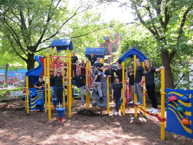 A team of volunteers help beautify a school playground with Teach for America
