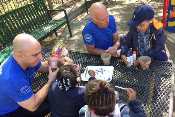 New York employees spending time with children on an art project.