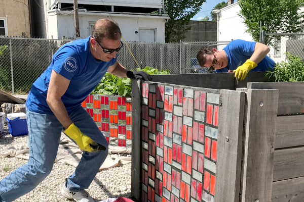 Employees in Wilmington installing a mosaic tile exhibit in a community youth garden.