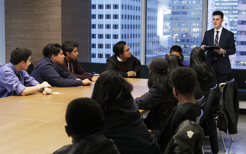 A Neuberger Berman employee leads a financial literacy lesson to Fiver students.